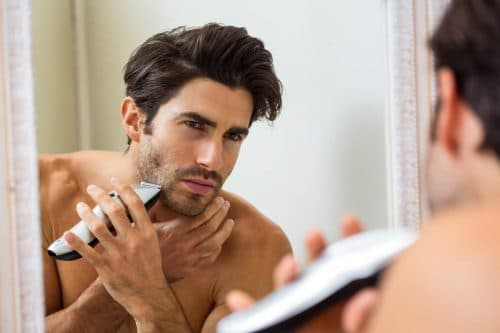young man shaving with beard stubble trimmer in front of mirror